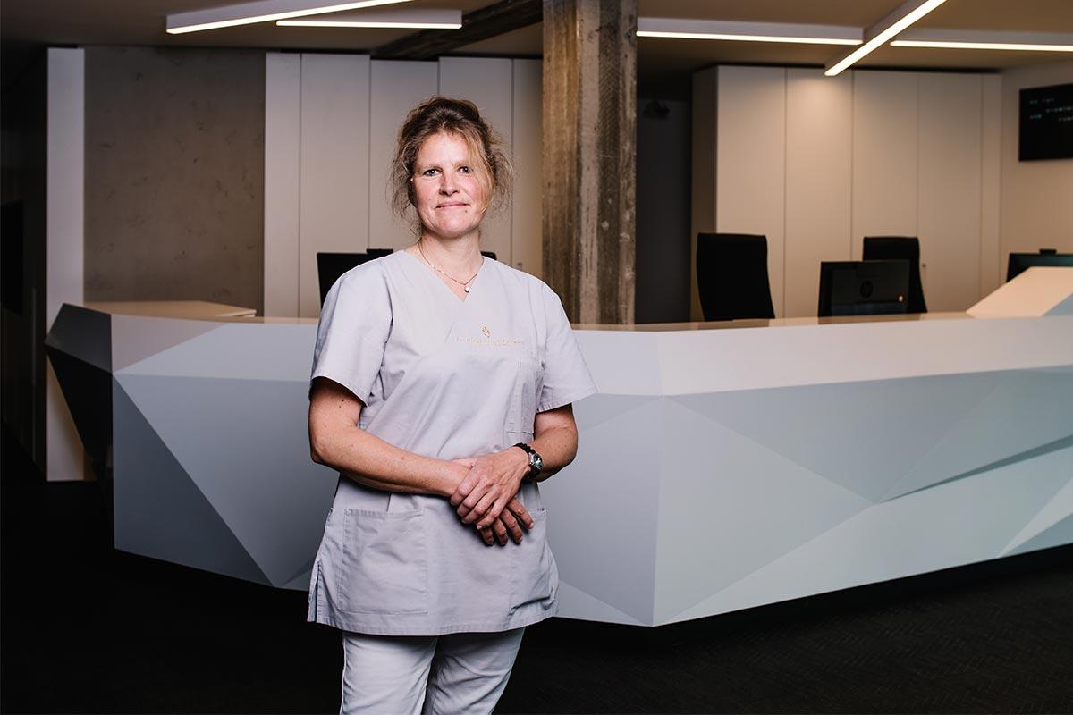 Frau Zaenker stehend vor Tresen in Praxis am Stadtpark in Hamburg á