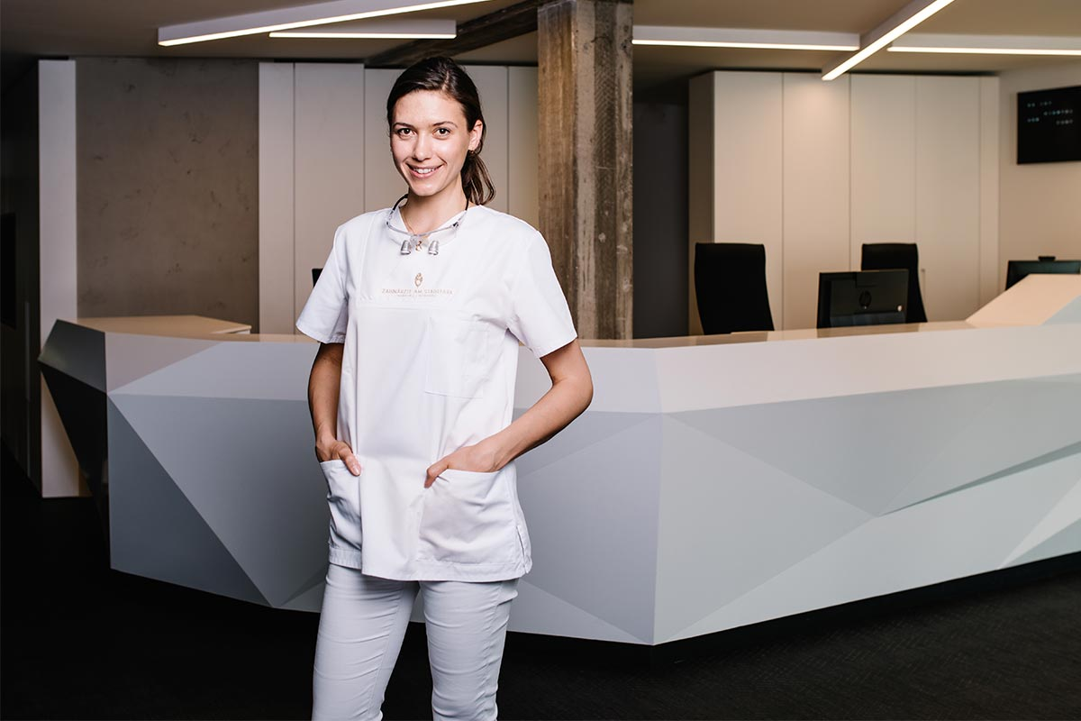 Zahnarzt Dr. Katja Boklage im Portrait stehend vor Tresen in der Praxis Zahnärzte am Stadtpark in Hamburg