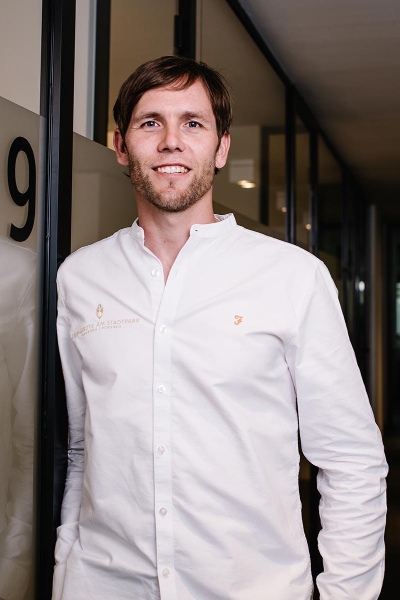 Zahnarzt Dr. Kristian Jährig im Portrait stehend